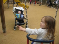 Nora showing Max how to use the swings.